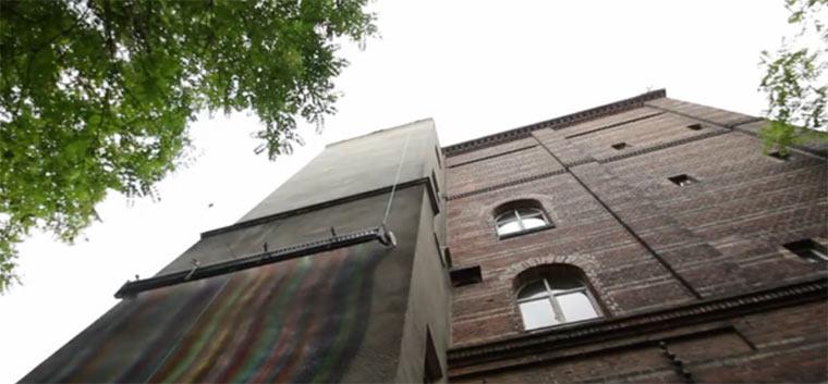 59 Spraydosen in Reihe bemalen eine Häuserwand