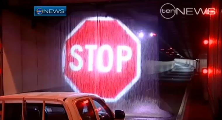 Stopschildprojektion auf Wasserwand stoppt zu hohen LKW vor Tunneleinfahrt