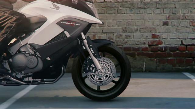 Das stehende Motorrad fährt durch die Wand