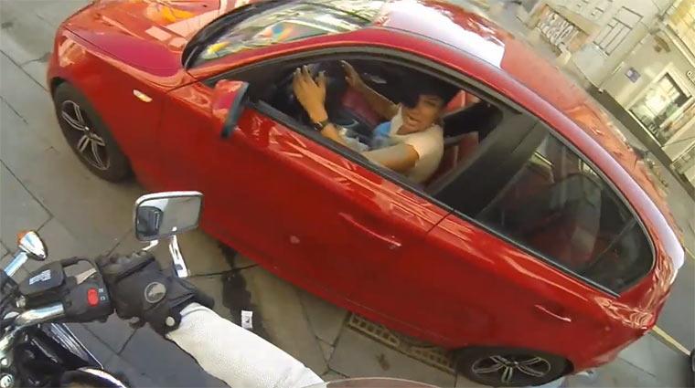 Frau wirft Müll in Autos zurück