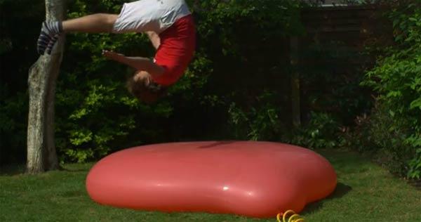 Slowmotionsprung auf gigantischen Wasserballon