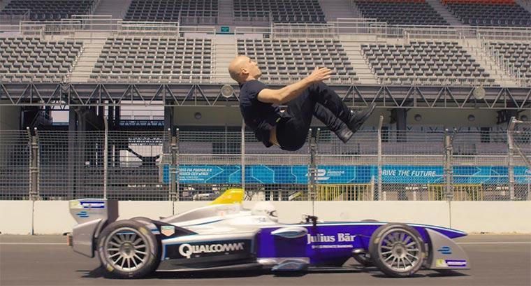 Damien Walters macht einen Backflip über einen fahrenden Formula E-Rennwagen