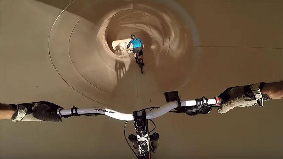 Auf dem Mountainbike durch die Wasserrutsche mountainbike-waterslide