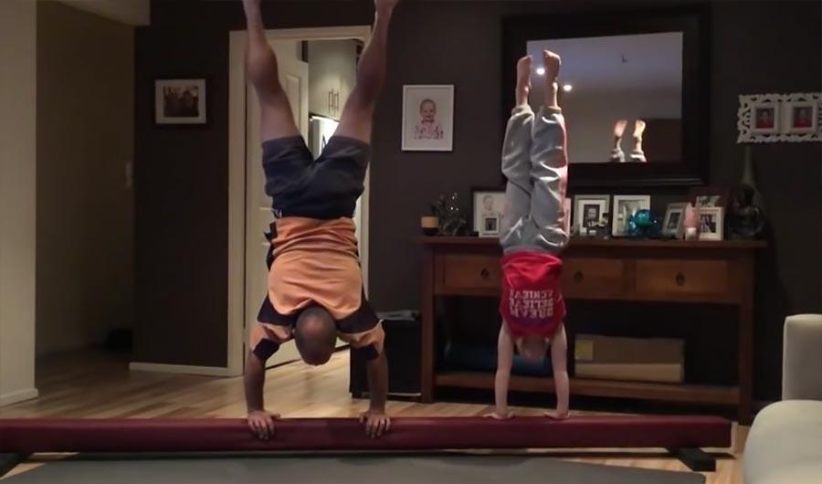 Vater versucht die Gymnastik-Übungen der Tochter nachzumachen