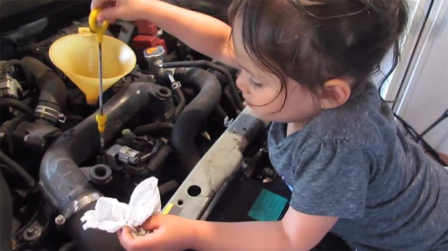 Dreijährige wechselt Öl und repariert Wasserhahn