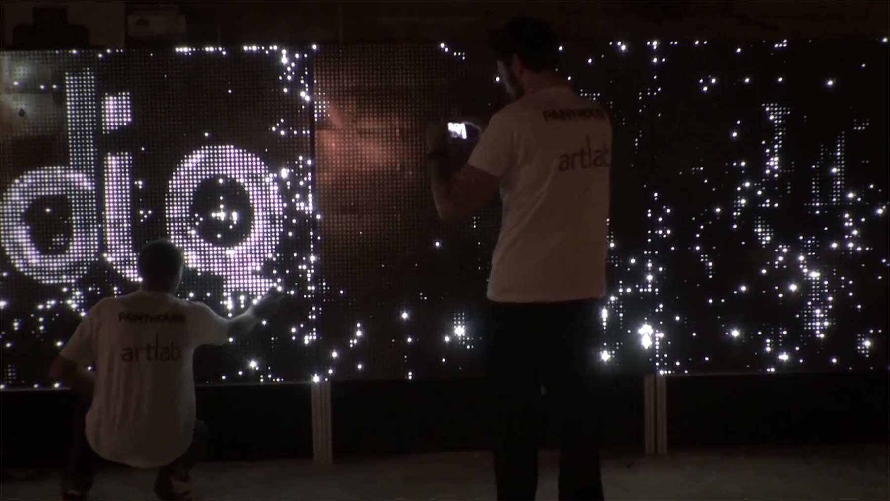 An einer LED-Wand wasseraktivierte Lichtbilder malen Water-light-graffiti