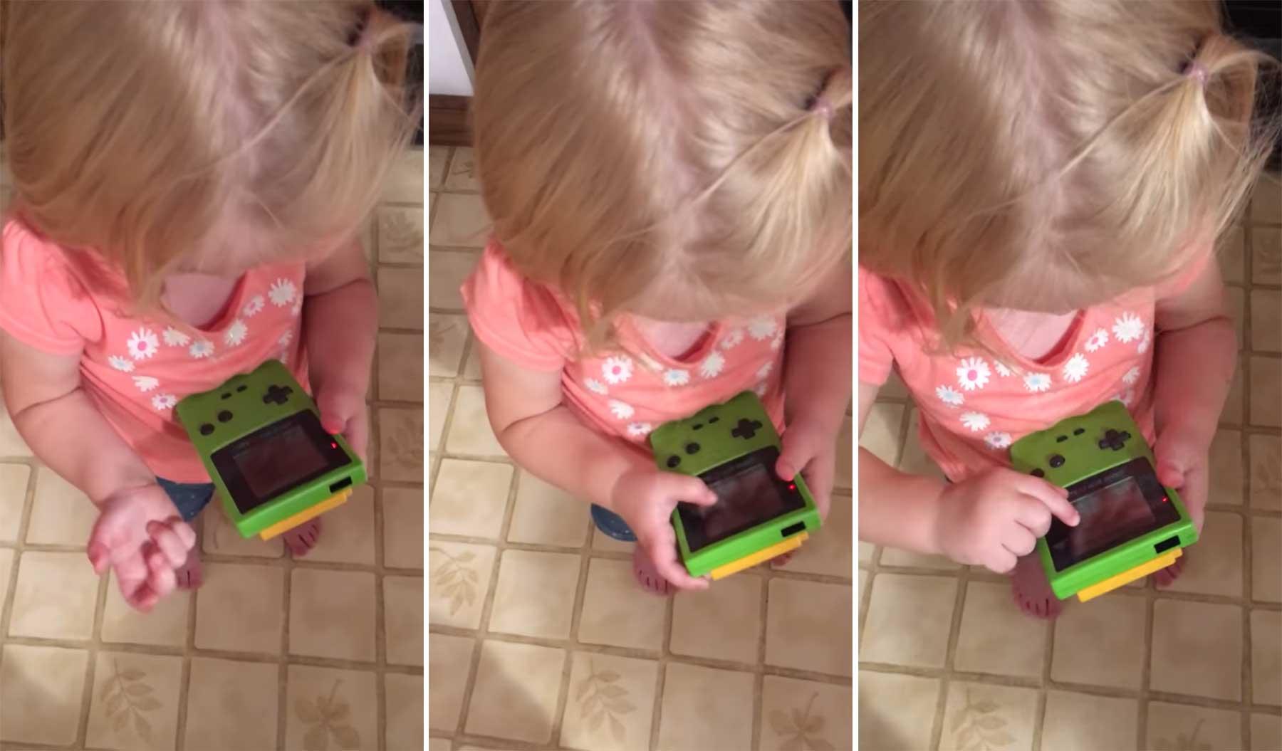 Ein Kind versucht, Game Boy zu spielen