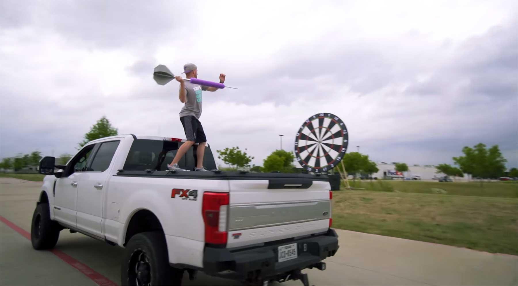 Gigantische Dartpfeile von fahrendem Truck auf riesige Dartscheibe werfen