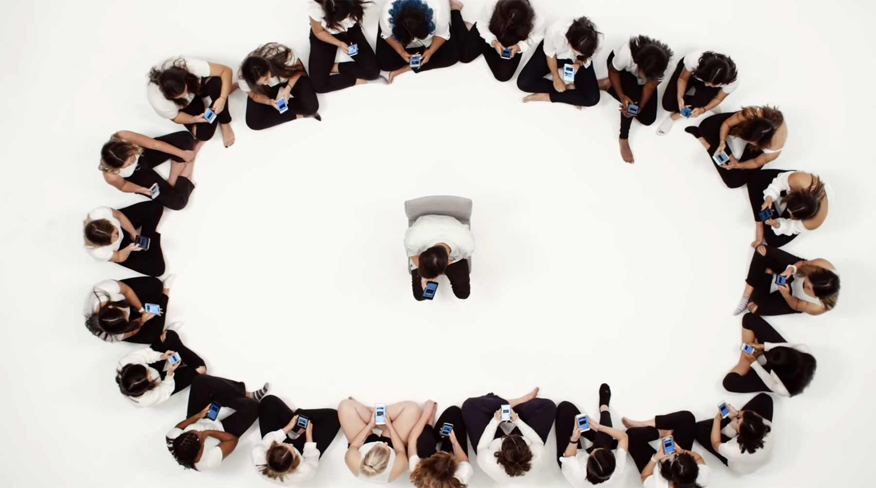 Ein Mann textet mit 20 Frauen, die um ihn herum sitzen