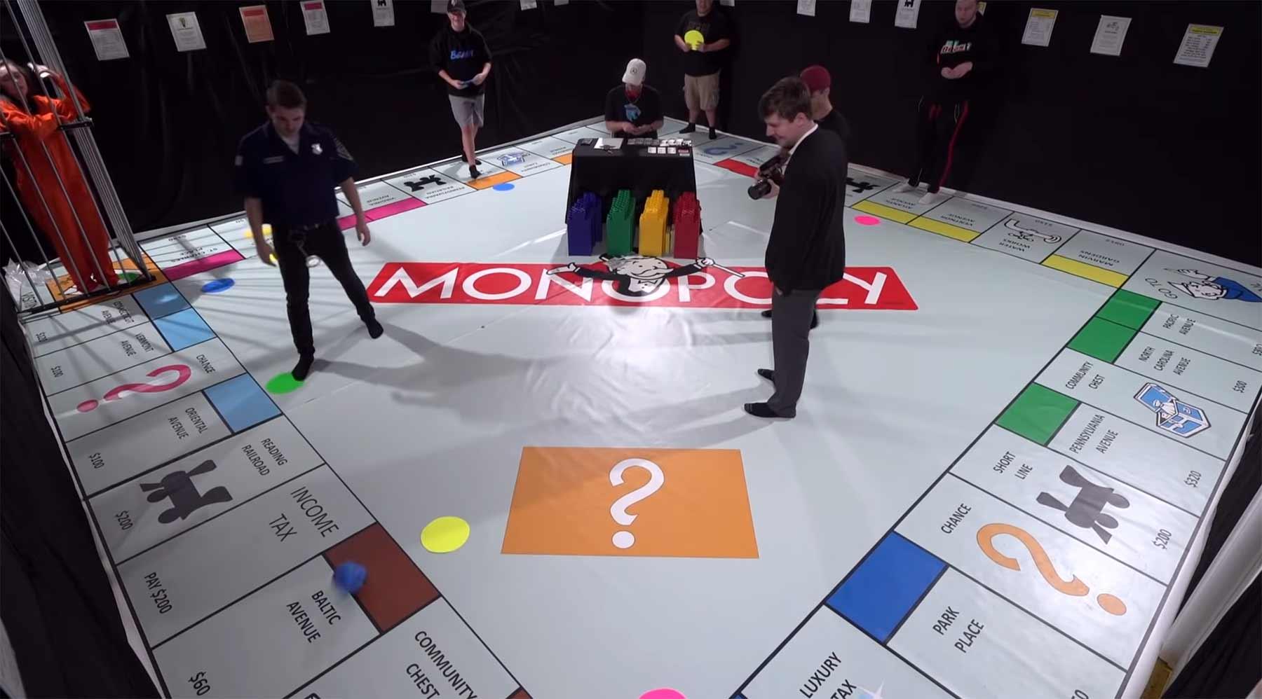 Riesiges Monopoly mit Menschen als Figuren und echtem Geld spielen