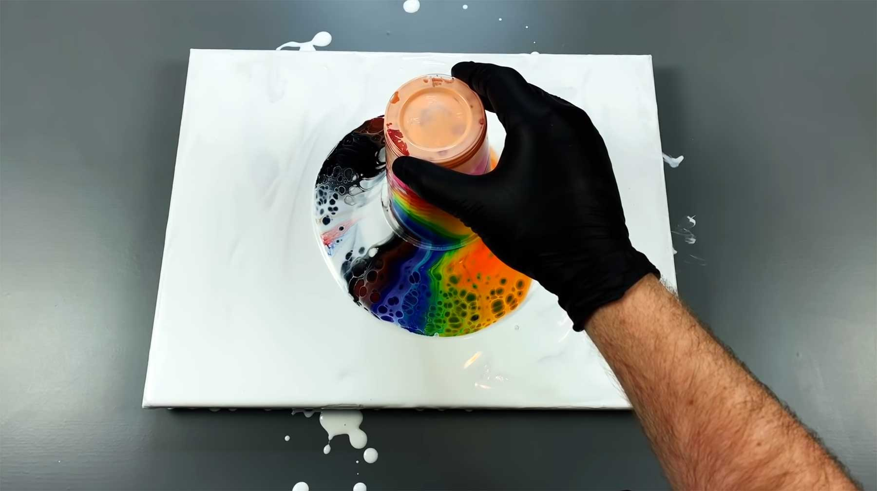 Einen Becher gemischter Acrylfarbe ausschütten