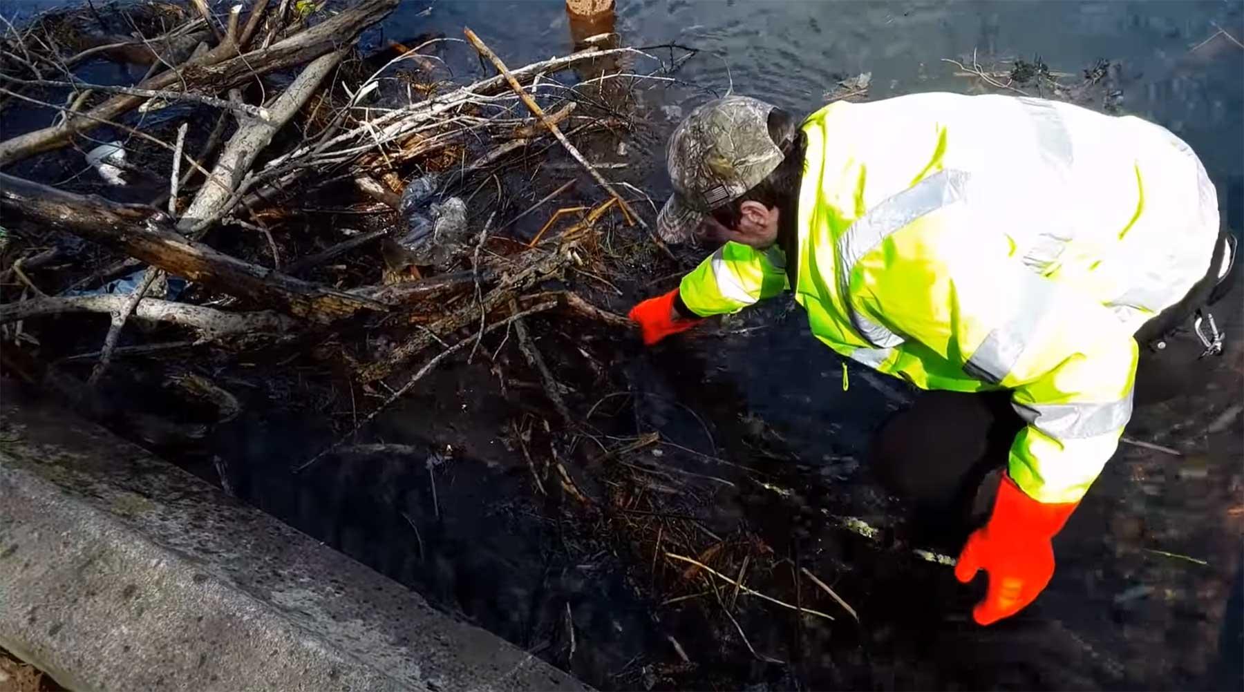 Nur ein Mann, der einen städtischen Abfluss entstopft stadtabfluss-reinigen