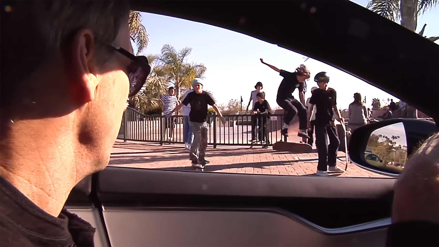 Tony Hawk fordert Skateboarder aus dem Auto heraus auf, einen Kickflip zu machen