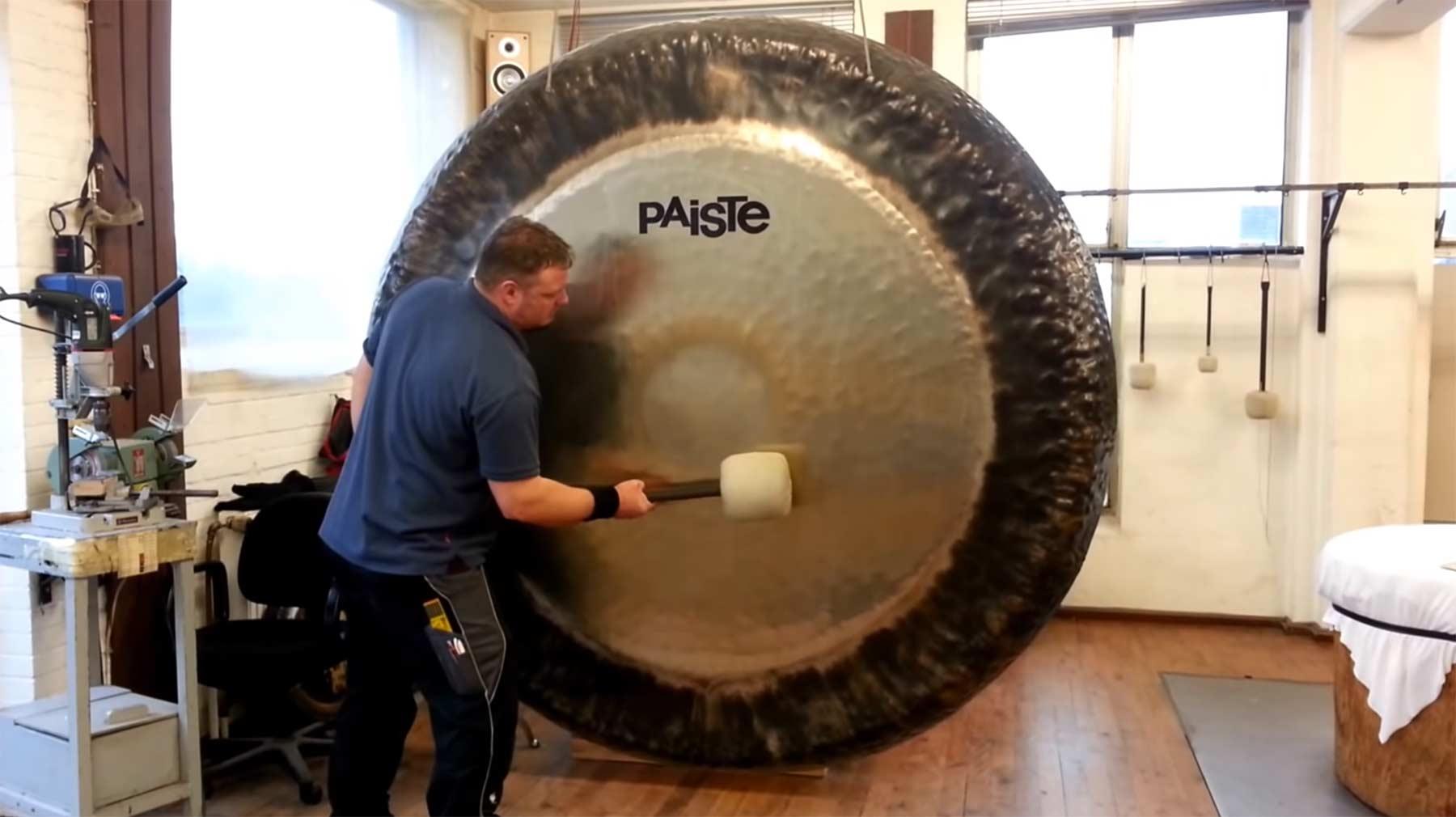 Einen zwei Meter großen Gong spielen