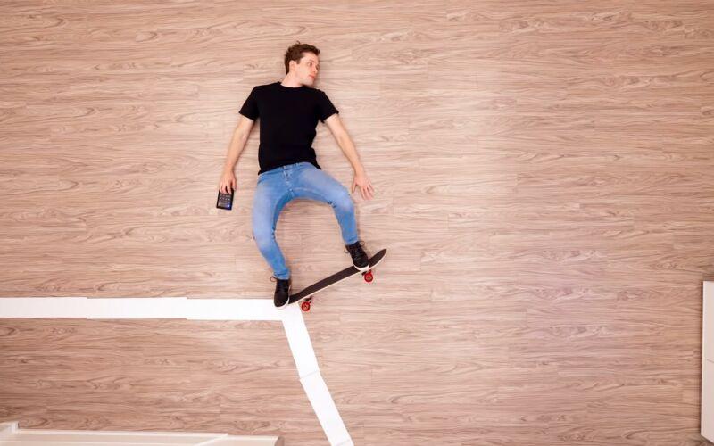 Kevin Parry fährt auf dem Boden liegend Skateboard