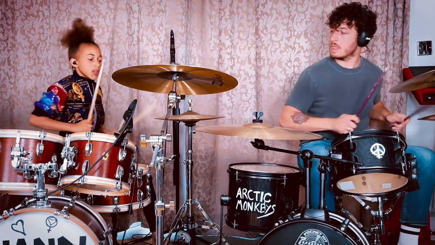 Nandi Bushell spielt Schlagzeug mit dem Drummer der Arctic Monkeys